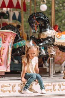 Aanbiddelijk meisje dichtbij de carrousel in openlucht