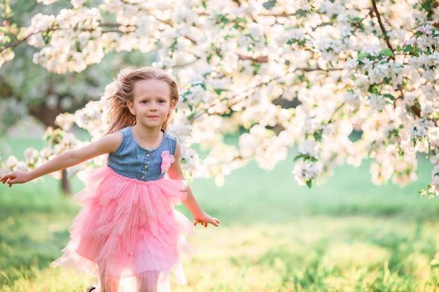 Aanbiddelijk meisje die de lente van dag in appel bloeiende tuin genieten