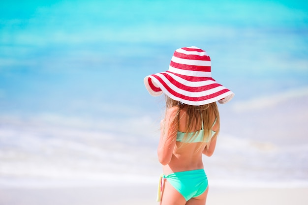 Aanbiddelijk meisje die in grote rode hoed langs wit zand caraïbisch strand lopen