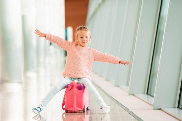 Aanbiddelijk meisje die in luchthaven met haar bagage op het inschepen wachten