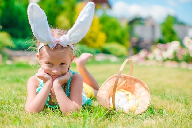 Aanbiddelijk meisje die konijntjesoren met paaseieren op de lentedag dragen