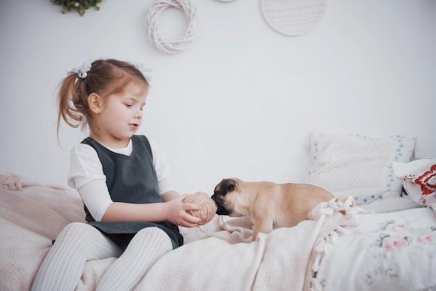 Aanbiddelijk meisje die leuke pug voeden. ze heeft een puppy gekocht. de beste vriend