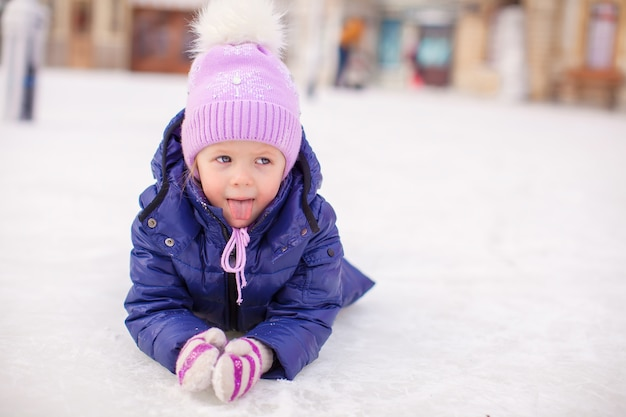 Aanbiddelijk meisje die op ijsbaan na de herfst leggen