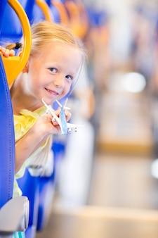 Aanbiddelijk meisje die op trein reizen en pret met vliegtuigmodel hebben in handen