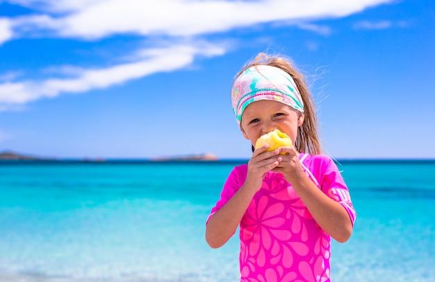 Aanbiddelijk meisje eet appel bij tropisch strand tijdens vakantie
