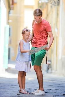 Aanbiddelijk meisje en gelukkige papa tijdens de zomer italiaanse vakantie in lege smalle straat