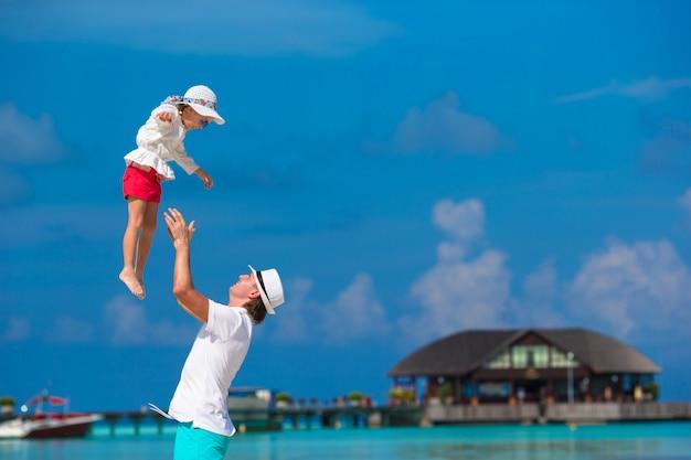 Aanbiddelijk meisje en gelukkige vader tijdens tropische strandvakantie