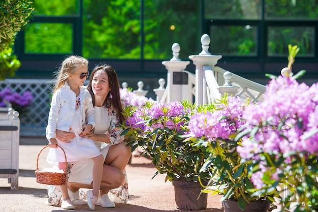 Aanbiddelijk meisje en jonge moeder die van warme dag in tulpentuin genieten