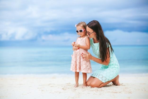 Aanbiddelijk meisje en jonge moeder op tropisch wit strand