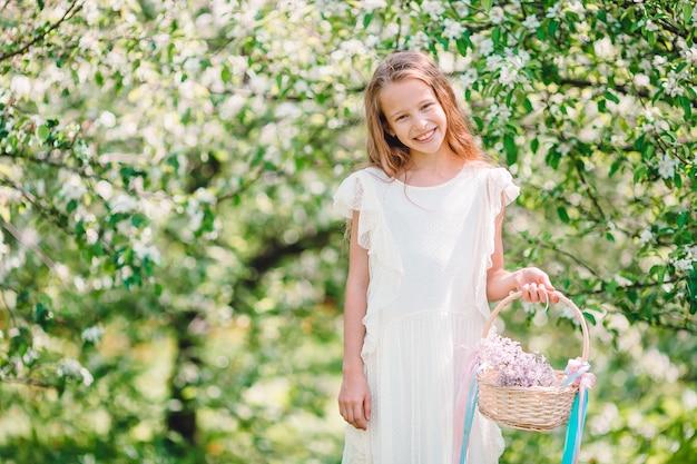 Aanbiddelijk meisje in bloeiende appeltuin op een mooie lentedag
