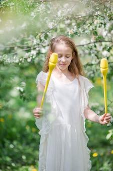 Aanbiddelijk meisje in bloeiende appeltuin op mooie de lentedag