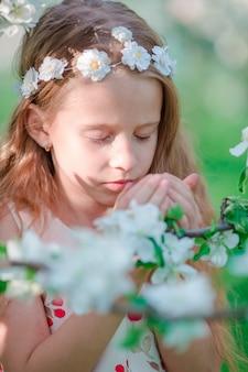 Aanbiddelijk meisje in de bloeiende tuin van de appelboom op de lentedag