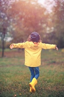 Aanbiddelijk meisje in het gele regenjas spelen onder de regen in het de herfstpark