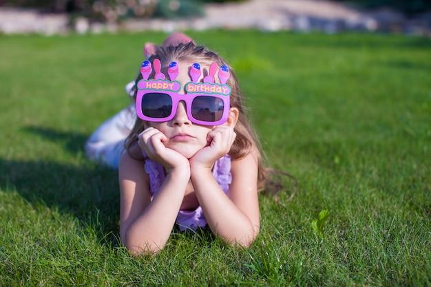 Aanbiddelijk meisje in het gelukkige verjaardagsglazen openlucht glimlachen