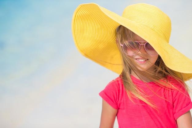 Aanbiddelijk meisje in hoed bij strand tijdens de zomervakantie
