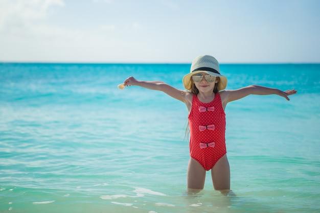 Aanbiddelijk meisje in hoed op strand tijdens de zomervakantie