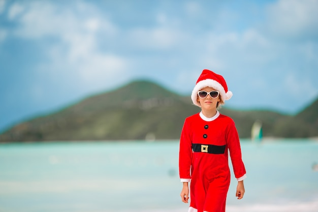 Aanbiddelijk meisje in kerstmanhoed op tropisch strand