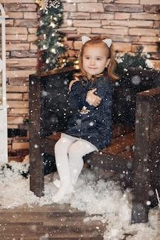 Aanbiddelijk meisje in kerstmisruimte die door kerstmisdecoratie wordt omringd