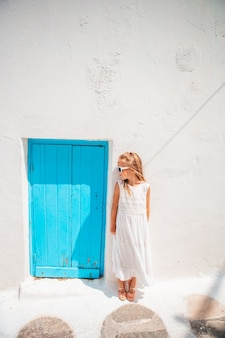 Aanbiddelijk meisje in kleding bij oude straat van typisch grieks traditioneel dorp met witte muur en blauwe deuren