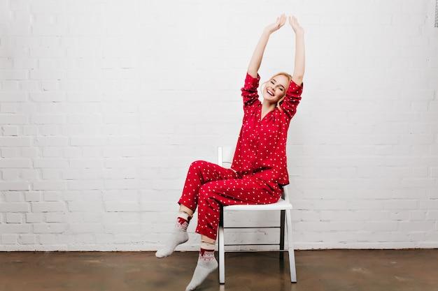 Aanbiddelijk meisje in leuke nachtkleding en sokken die op stoel zitten en lachen. indoor portret van positieve jonge vrouw in rode pyjama's die zich uitstrekt met een glimlach.