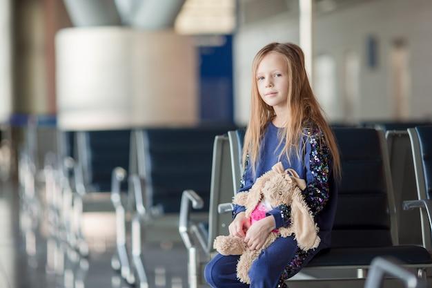 Aanbiddelijk meisje in luchthaven dichtbij groot venster binnen