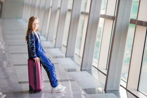 Aanbiddelijk meisje in luchthaven dichtbij groot venster
