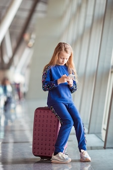 Aanbiddelijk meisje in luchthaven dichtbij het grote venster spelen met haar telefoon