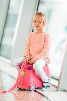 Aanbiddelijk meisje in luchthaven met haar bagage die op het inschepen wachten