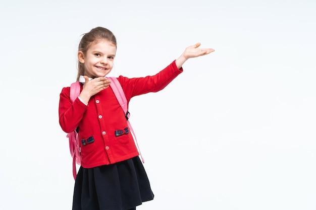 Aanbiddelijk meisje in rode de kledingsrugzak van het schooljasje