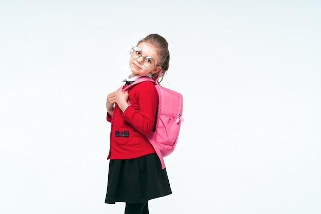 Aanbiddelijk meisje in rood schooljasje, zwarte kleding, ronde glazen die de riemen van een rugzak vasthouden en glimlachend en bekijkend de camera, die op witte ruimte stellen. isoleren