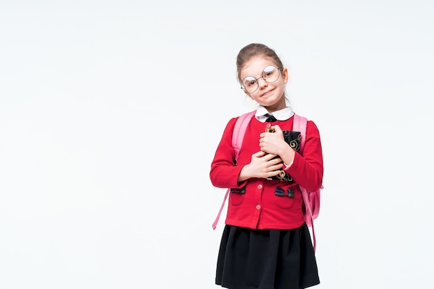 Aanbiddelijk meisje in rood schooljasje, zwarte kleding, rugzak en ronde glazen omhelst strak een boek en glimlacht terwijl het genieten van en het stellen op witte ruimte. isoleren