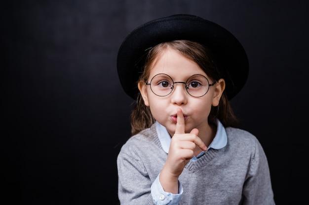 Aanbiddelijk meisje in slimme vrijetijdskleding en bril die u vraagt te zwijgen over geïsoleerde zwarte ruimte