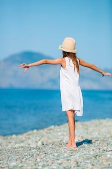 Aanbiddelijk meisje in wit op het strand dat pret heeft