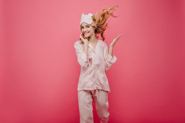 Aanbiddelijk meisje in zijden nachtkostuum dat op roze muur danst. mooie vrouw met golvend haar ochtend doorbrengen