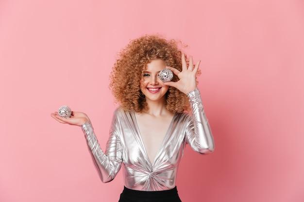Aanbiddelijk meisje met blonde krullen gekleed in zilveren blouse glimlacht en stelt met discoballen op roze ruimte.