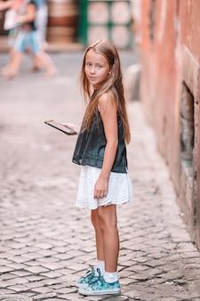 Aanbiddelijk meisje met celtelefoon bij italiaanse stad tijdens de zomervakantie