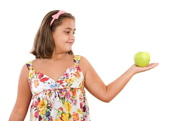 Aanbiddelijk meisje met gebloeide kleding met een appel op een witte achtergrond