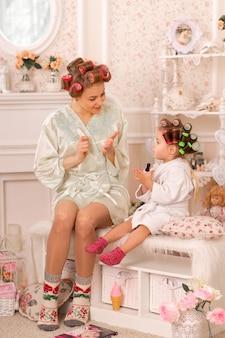 Aanbiddelijk meisje met haar moeder in krulspelden schilderen hun vingernagels. kopieert het gedrag van mama. moeder leert haar dochter om voor zichzelf te zorgen. schoonheid dag.