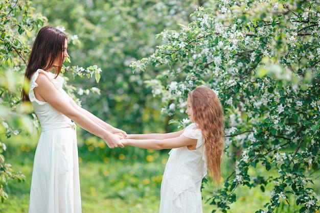 Aanbiddelijk meisje met jonge moeder in bloeiende kersentuin op mooie lentedag