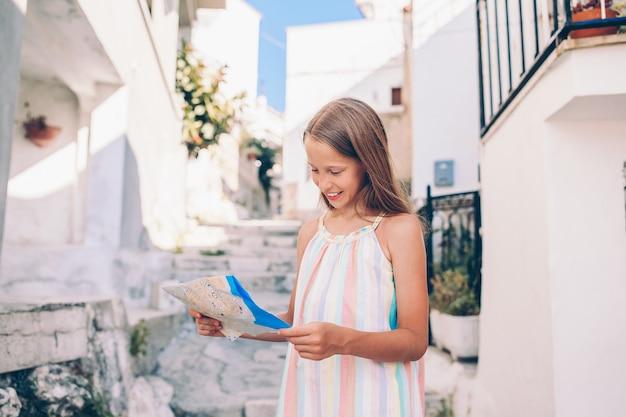 Aanbiddelijk meisje met kaart van europese stad in openlucht
