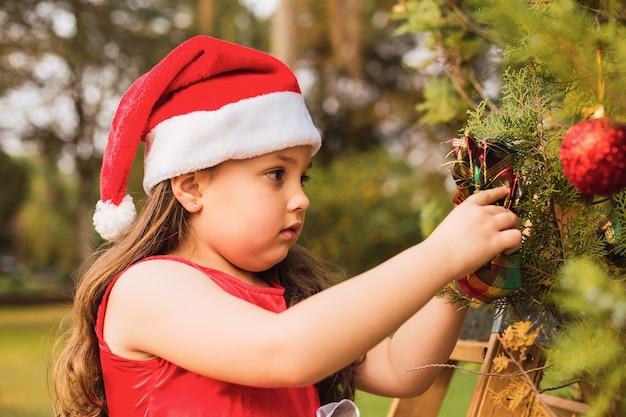 Aanbiddelijk meisje met kerstmuts legt een bal op de kerstboom