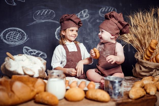 Aanbiddelijk meisje met kind bij lijst het koken
