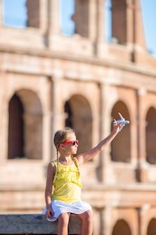 Aanbiddelijk meisje met kleine stuk speelgoed modelvliegtuigachtergrond colosseum in rome, italië