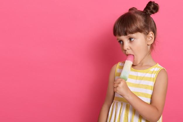 Aanbiddelijk meisje met knopen in gele en witte zomerjurk die roomijs op roze achtergrond eten, ruimte voor reclame of promotietekst kopiëren.