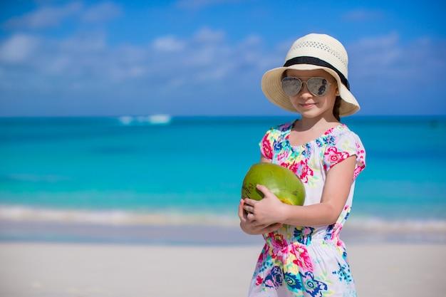 Aanbiddelijk meisje met kokosnoot bij wit strand tijdens de zomervakantie