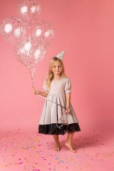 Aanbiddelijk meisje met kostuum en ballons