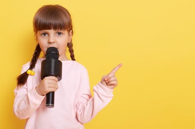 Aanbiddelijk meisje met microfoon op gele muur, terwijl gesprek in mic, wijsvinger opzij richt. kopieer tempo.