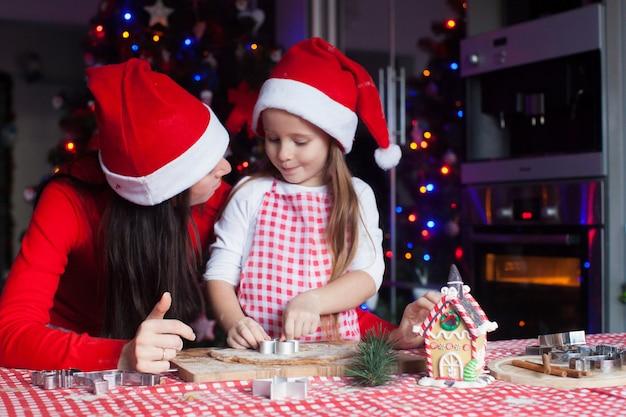 Aanbiddelijk meisje met moeder die santahoeden dragen die de koekjes van de kerstmispeperkoek samen bakken