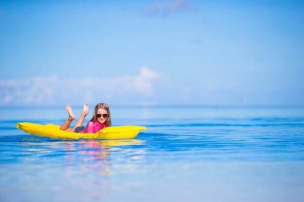 Aanbiddelijk meisje met opblaasbare luchtmatras in openlucht zwembad