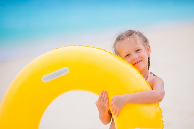 Aanbiddelijk meisje met opblaasbare rubbercirkel op wit strand klaar om te zwemmen